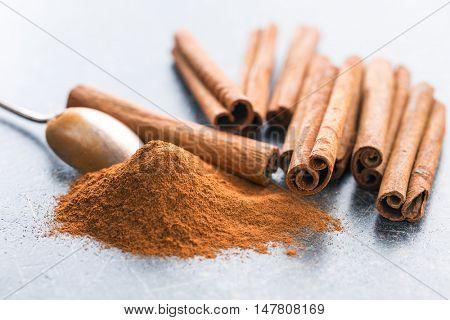 Cinnamon sticks and ground cinnamon on kitchen table.