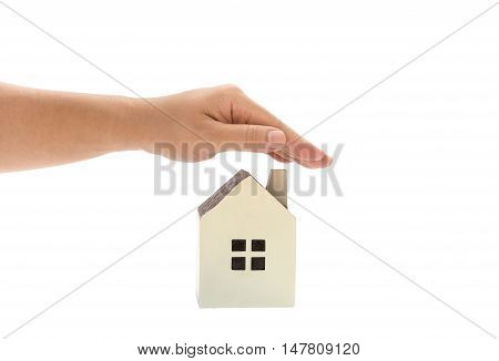 left hand covering a small family house home insurance concept or representing home ownership