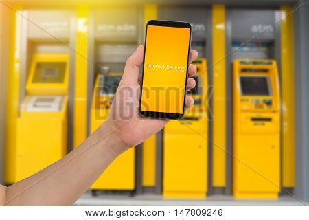 human hand hold smart phone tablet cellphone with virtual app internet banking on blurry Automatic Teller Machine Background Online banking Concept.