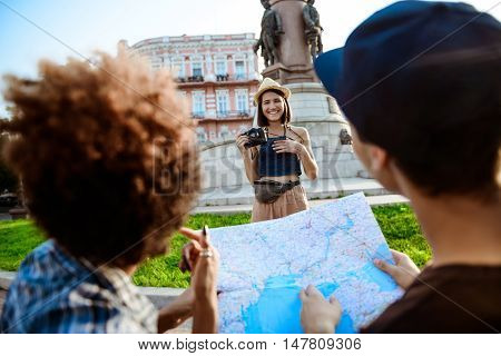Young beautiful female tourist in hat taking picture of her friends holding map, sitting back to camera.