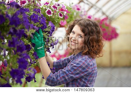 happy female nursery worker trimming plants in greenhouse