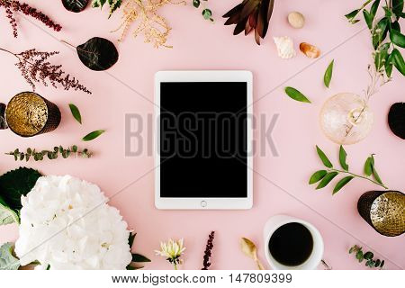 creative decorated and arranged flat lay frame concept with tablet vintage tray hydrangea shells coffee golden spoon branches on pink background. top view