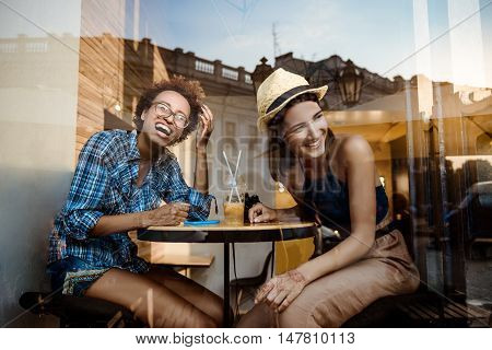 Two young beautiful girls smiling, laughing, resting, sitting in cafe