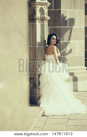 young sexy girl with brunette hair and pretty face in white wedding bride long dress posing near stony building wall sunny outdoor copy space
