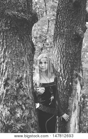 Young Girl In A Long Fantasy Black Dress Posing In An Autumn Forest, Black And White Photo