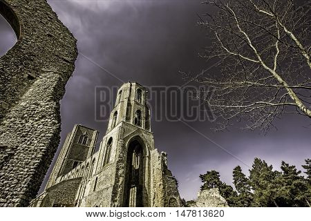 This is a picture of the partly ruined Wymondham Abbey a magnificent Norman church in Norfolk UK. It was established in 1107. The tone emphasises the dramatic nature of the building as does the perspective which also allows some central copy space.