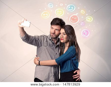 A cheerful young couple taking selfie photo with mobile phone and colorful happy smiley faces illustration above them concept