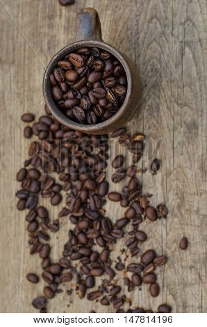 Roasted coffee beans in a plain ceramic mug on a wooden background top view