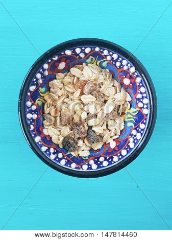 muesli in a bowl on a turquoise background
