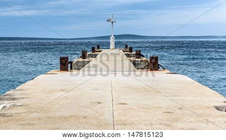 Old pier with a lighthouse beacon and calm sea. Rusty moorings and seagulls on concrete pier on a windy day with dramatic clouds. Adriatic sea - Silba Croatia.