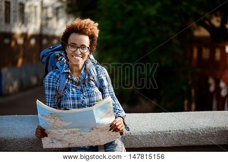 Young beautiful african female traveler in glasses with backpack smiling, holding map, looking at camera outdoors.