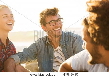 Three friends enjoying together at sunset. Young woman and smiling man with spectacles having fun with friends. Happy guys and girl in casual sitting outdoor.