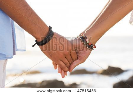 Closeup of young couple holding hands at beach during sunset. Close up hands of young man and woman. Lovers couple holding hands in summer.