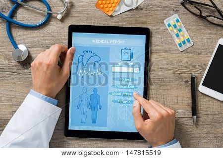 High angle view of doctor hand checking medical report on digital tablet. Doctor checking patient health history. Top view of male doctor hands using tablet at clinic to review mediacal report.
