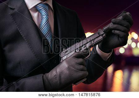 Murderer Or Killer Holds Pistol With Silencer In Hands At Night.