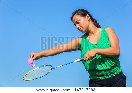 Dutch woman serve with badminton racket and shuttle against blue sky