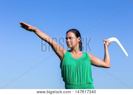european woman throwing white boomerang in blue sky