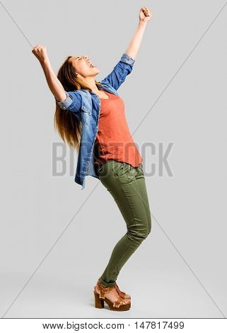 Beautiful happy woman with arms up over a gray background
