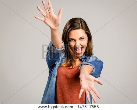 Beautiful happy woman showing her hands over a gray background