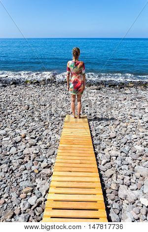 Woman standing on wooden path at stony beach and ocean