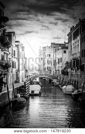 Gondolas or boats on Grand canal in beautiful town Venice. Black and white photo