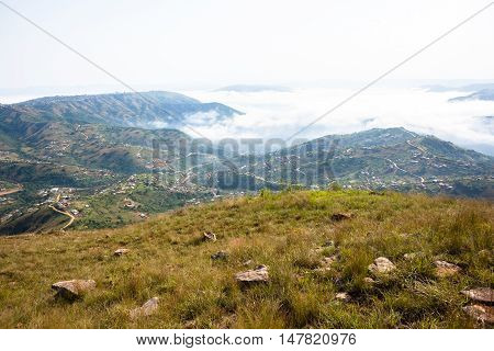 Clouds mist moves through rural valley hills covering homes over scenic landscape.
