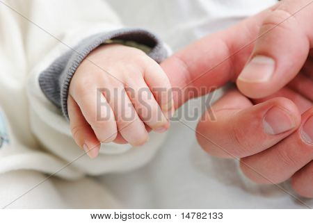 Newborn baby holding father's finger