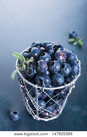 Freshly picked blueberries in metallic cup on blue background. Concept for healthy eating and nutrition with copy space.