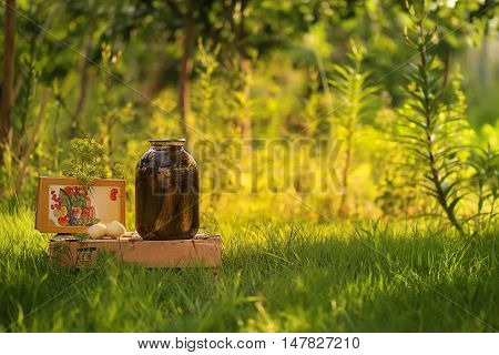 Pickles glass bank. cucumbers are marinaded. Some Herbal a bunch of dill book of seaming on the wooden box . Bank for closing for roll blending. Outdoor still-life
