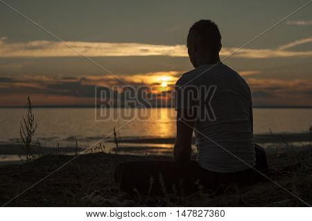 Young man doing yoga exercises on the beach at sunset. Meditation Pose.