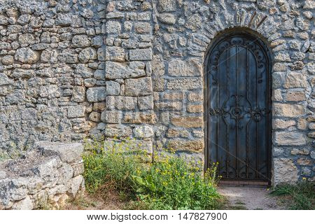 Heavy closed black metal door on a stone wall of a medieval fortress, made of riveted wood. Free spase for text.