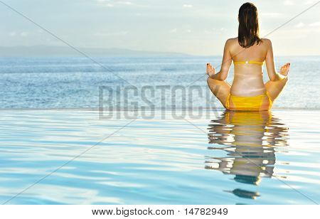 Woman doing yoga exercise at poolside