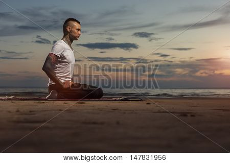 Serene young man with tattoos practicing yoga on the beach. Summer time, sunset.