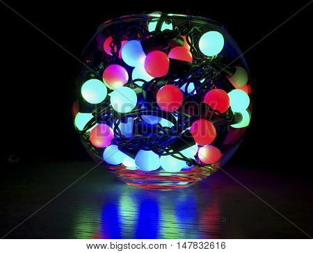 garland with colorful round lights placed in a semi-circular glass dishes, in darkness, new year, Christmas, holiday
