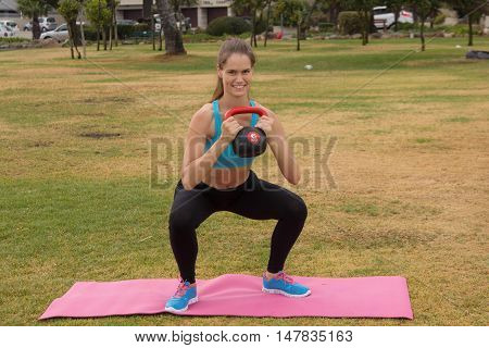 A pretty woman in exercise clothing doing lunges with a kettlebell weight in the outdoors