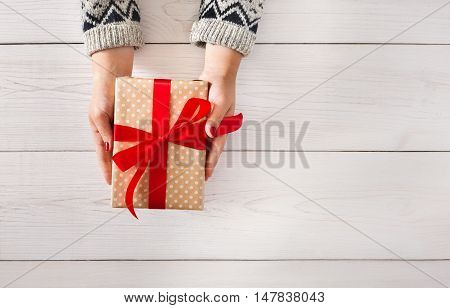 Woman's hands give wrapped christmas or other holiday handmade present in paper with red ribbon. Present box, decoration of gift on white wooden table, top view with copy space