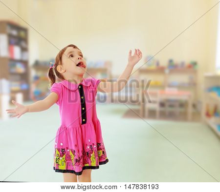Surprised little girl raised his head up and gesturing with his hands. Close-up.On blurred background the great hall of the kindergarten, with long racks where there are toys.