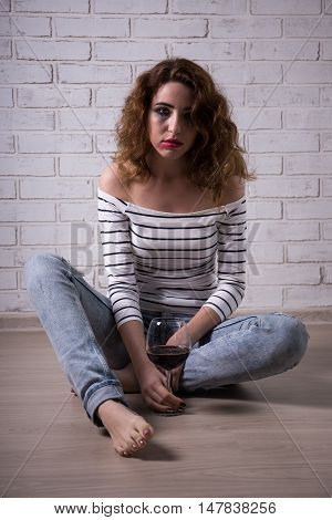 Young Woman Sitting On The Floor With Glass Of Wine