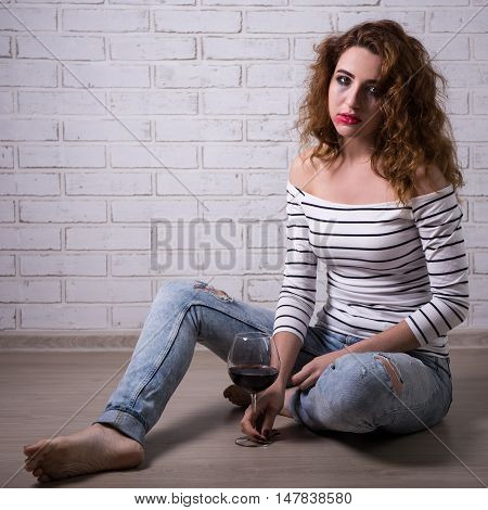 Female Alcoholism - Young Woman Sitting On The Floor With Glass Of Wine