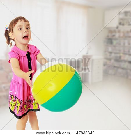 Emotional little girl with pigtails on the head , in a pink dress. Girl catches with hands a large, inflatable striped ball.In the background children's room, where the shelves are containers