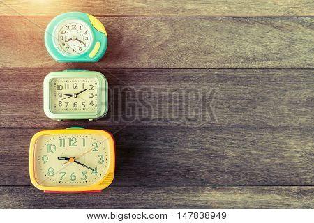 Retro alarm clocks on wood table. Retro or vintage color filtered. Old time concept. Nostalgia concept.
