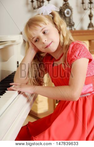 Sad little girl in a long orange dress, with long blonde hair braided in pigtails . Close-up