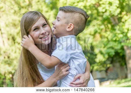 outdoor portrait of young handsome child boy with his mother