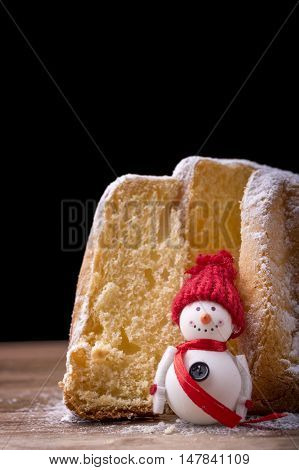 pandoro cake with icing sugar and snowman on wood on black background