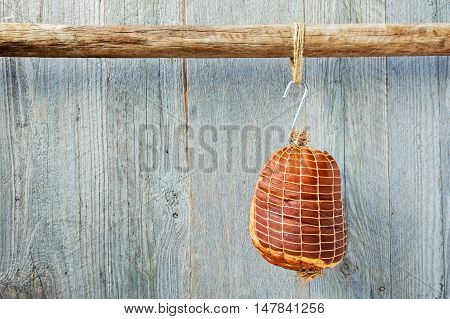 Smoked boneless pork ham hock wrapped in netting hanging on a hook from a wooden pole with a weathered wood background