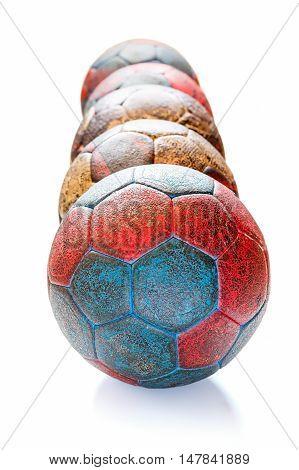 Row of five dirty handball balls isolated on white