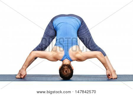 Beautiful sporty fit woman practices Ashtanga Vinyasa yoga asana Prasarita padottanasana D - wide legged forward bend D isolated on white