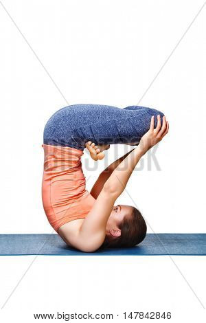 Sporty fit yogini woman practices inverted yoga asana Urdhva padmasana - lifted lotus pose isolated on white