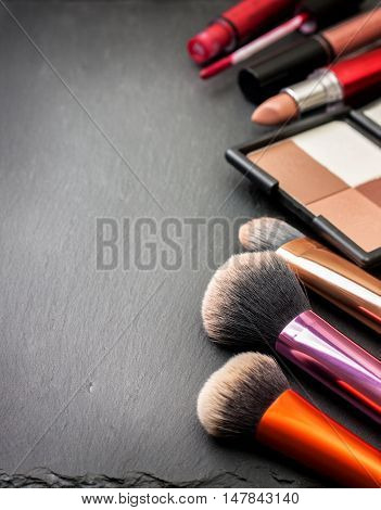 makeup brushes cosmetics on black stone background