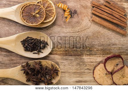 star anise, cloves and dried orange on wooden spoon with cinnamon and dried apple